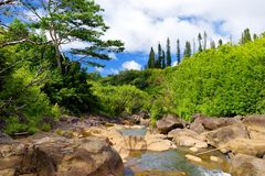 Beautiful view of a stream flowing between rocks, located along famous Road to Hana on Maui island, Hawaii. USA Stock Image