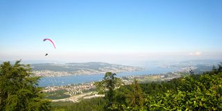 Beautiful view in sunny summer weather over yachts, sailboats and paragliding sports on Lake Zurich stock photos