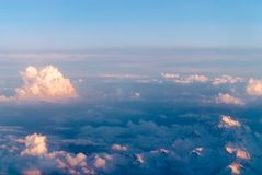 Beautiful view at sunset. Beautiful view above cloudscape and mountains at sunset from plane Royalty Free Stock Images