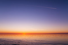 Beautiful view of the sunset over a sea. With waves, ripples, clear sky and trace of a plane. Baltic sea, Latvia Stock Photo
