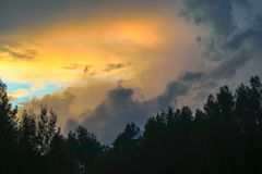 Beautiful view of sunset storm cloud formation enlightened with last yellow sunbeams and visible blue sky royalty free stock image