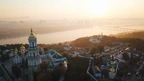 Beautiful view to Kiev Pechersk Lavra, rider Dnipro. Aerial drone video footage. Fog and sunrise light. European capital. Most visited palces. Beautiful golden stock footage