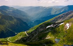 Beautiful view in to the valley of fagars mountain. Lake among the grassy slopes and rocky cliffs. unforgettable vacation in Romania Royalty Free Stock Photography