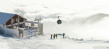 Beautiful view from the top of a moutain with cable cars going up above clouds Royalty Free Stock Photos