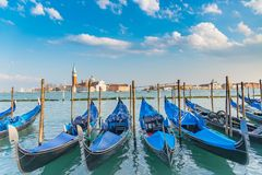 Gondolas in Venice. The beautiful view of traditional Gondola boat on canal with historic Basilica di Santa Maria della Salute in the background on a sunny day Royalty Free Stock Image