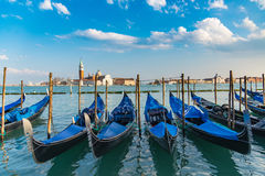 Gondolas in Venice. The beautiful view of traditional Gondola boat on canal with historic Basilica di Santa Maria della Salute in the background on a sunny day Royalty Free Stock Photography