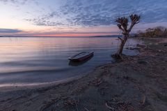 Beautiful view of Trasimeno lake Umbria at dusk, with a little boat near a bare tree, perfectly still water and a. Beautiful view of Trasimeno lake Umbria at stock photography