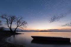 Beautiful view of Trasimeno lake Umbria at dusk, with a little boat silhouette in the foreground, perfectly still. Beautiful view of Trasimeno lake Umbria at Stock Photo