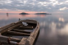 Beautiful view of Trasimeno lake Umbria at dusk, with a little, old boat partially filled by water, perfectly still. Water and a mackerel sky royalty free stock photography