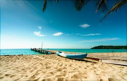 Beautiful view tropical paradise beach of resort. Coconut tree, wooden bridge, and kayak at resort on sunny day. Summer vacation stock images