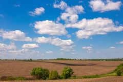 Beautiful view of untilled fields and beauty cloudy sky. Royalty Free Stock Photo