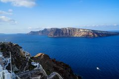 Beautiful view of vast blue Aegean sea, sailing ships and natural caldera mountain from Oia village with white buildings. Along island with blue sky background Royalty Free Stock Photo