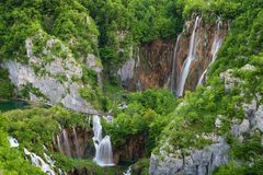 Beautiful view of waterfalls with turquoise water and wooden pathway through over water. Plitvice Lakes National Park, Croatia. Fa Stock Image