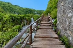 Beautiful view of waterfalls with turquoise water and wooden pathway through over water. Plitvice Lakes National Park, Croatia. Fa royalty free stock images