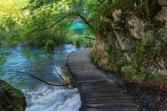 Beautiful view of waterfalls with turquoise water and wooden pathway through over water. Plitvice Lakes National Park, Croatia. Fa Stock Photos