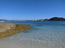 Beautiful view of white sand beach and blue and crystalline water with clear sky on the beach Rhodes Cies Islands. stock photo
