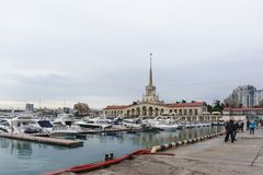 Beautiful view of white yachts and boats at the pier in the waters of the seaport of Sochi on a cloudy spring evening Royalty Free Stock Photos
