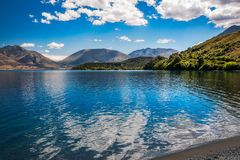 Beautiful View at Wilson Bay, Otago, New Zealand. Beautiful View of Lake Wakatipu with clouds reflections in the water at Wilson Bay, Otago Region, New Zealand Stock Photos