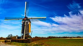Beautiful view of a windmill next a field on a wonderful sunny day. Beautiful view of a windmill next a field, wonderful sunny day with white clouds of irregular stock images