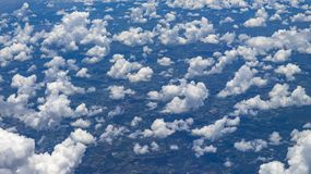 Beautiful view from window of plane flying over clouds. Natural panorama with clouds. White clouds moving above the ground royalty free stock images