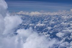 Beautiful view from window of plane flying over clouds. White clouds moving above the ground. Beautiful view from window of plane flying over clouds. Natural stock photo