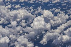 Beautiful view from window of plane flying over clouds. Natural panorama with clouds. White clouds moving above the ground royalty free stock photos