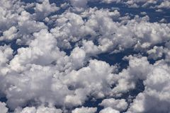 Beautiful view from window of plane flying over clouds. Natural panorama with clouds. White clouds moving above the ground royalty free stock image