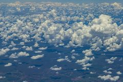 Beautiful view from window of plane flying over clouds. Natural panorama with clouds. White clouds moving above the ground stock image