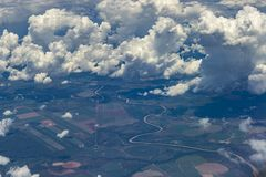 Beautiful view from window of plane flying over clouds. White clouds moving above the ground. Beautiful view from window of plane flying over clouds. Natural stock images