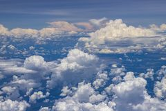 Beautiful view from window of plane flying over clouds. White clouds moving above the ground. Beautiful view from window of plane flying over clouds. Natural royalty free stock image