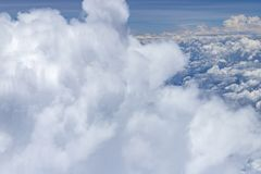 Beautiful view from window of plane flying over clouds. White clouds moving above the ground. Beautiful view from window of plane flying over clouds. Natural royalty free stock photos