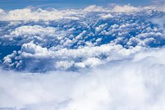 Beautiful view from window of plane flying over clouds. White clouds moving above the ground. Beautiful view from window of plane flying over clouds. Natural royalty free stock images