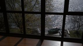 Beautiful view from window on splashing sea on sunny day. From panoramic window there is wonderful picture - wooden boat standing by picturesque shore, green stock video footage