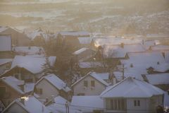 Beautiful view of winter morning fog, snow and sun filling on landscape of houses and buildings in Belgrade. Scenery during sunrise, sunset of top view at stock image