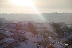 Beautiful view of winter morning fog, snow and sun filling on landscape of houses and buildings in Belgrade. Scenery during sunrise, sunset of top view at stock photos