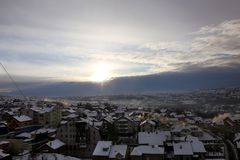 Beautiful view of winter morning fog, snow and sun filling on landscape of houses and buildings in Belgrade. Scenery during sunrise, sunset of top view at royalty free stock photo
