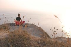 Beautiful view of woman doing yoga on the mountain with sea view at sunset. Back view. Beautiful view of woman doing yoga on the mountain with sea view at stock image