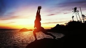 Beautiful view of woman doing yoga stretching on the rock with sea view at sunset. slow motion. 1920x1080. Beautiful view of woman doing yoga stretching on the stock video footage