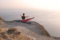 Beautiful view of woman doing yoga Upavistha Konasana, Wide Seated Forward Bend Pose on the mountain with sea view at stock photo