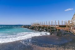 Beautiful view. wooden pier on the shore and stones. The wave is approaching the shore stock photos