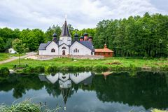 Beautiful views of the ancient white-stone Orthodox monastery of St. John the Evangelist with the reflection in the pond. Stock Photo