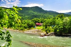 Beautiful views of the Caucasus mountains and a small village on the banks of the river. A small village on the banks of a mountain river. Nikitino. Psebay Stock Photography