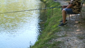 Beautiful views of forest lake with reflection. Fisherman with a fishing rod. Beautiful views of forest lake with reflection of green trees and grass. Fisherman stock footage