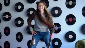 The beautiful vigorous girl poses for the camera with a guitar against the background of vinyl records. The girl has fun stock video footage
