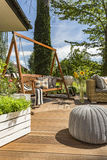 Beautiful villa patio idea. New villa patio with garden swing, small pouf and wooden flooring Royalty Free Stock Photo