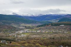 Beautiful village of Bierzo surrounded by snowy mountains and a cloudy sky. Village of the Bierzo valley surrounded by vegetation with snowy mountains in the royalty free stock image