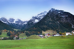 Beautiful village between snow covered mountains Stock Photos