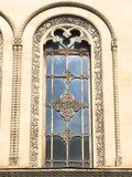 Beautiful vintage ancient old carved window with glass with a forged frame arches and patterns. The background stock photo