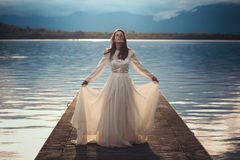 Beautiful vintage bride on a lake pier Stock Images