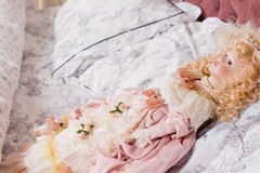 Beautiful vintage doll lying on a pillow Stock Photo